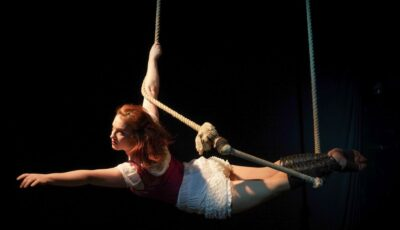 An aerial performer hanging onto a rope