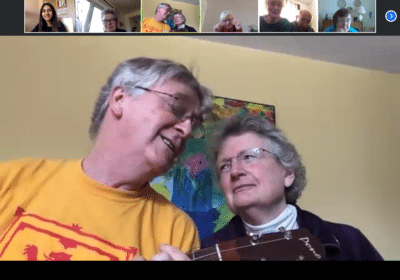 A screenshot of a video call, a large box with two older people with grey hair sat together, one playing a guitar, with a row of smaller boxes at the top showing the other callers