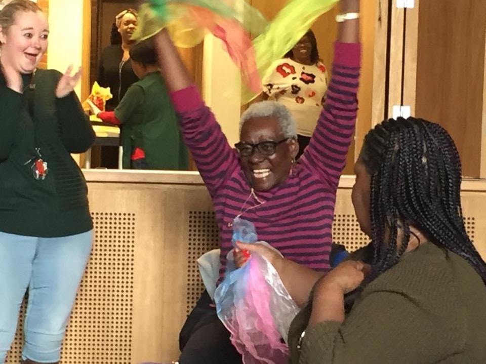An older woman cheers while a younger volunteer looks on and applauds