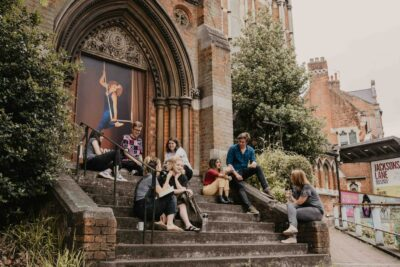 A group of artists sit on the steps of the Jacksons Lane theatre