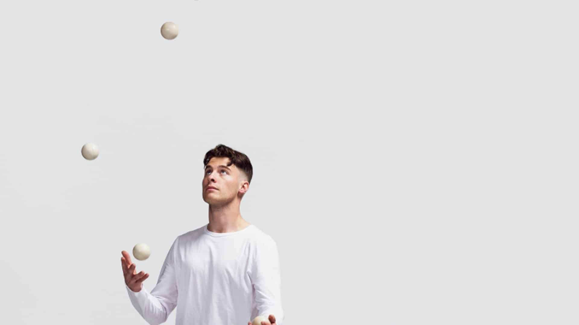A person in a long sleeved white t-shirt juggling three balls