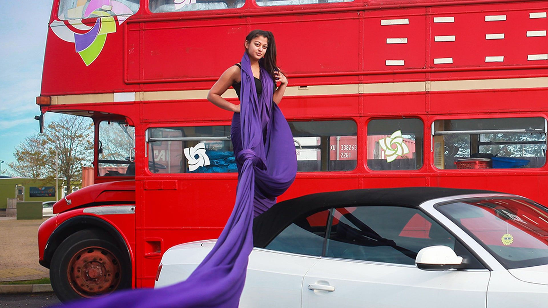 A person wearing a purple dress with a lush long purple train from their neck stood on the back of a white soft top convertible car in front of a classic red double decker bus