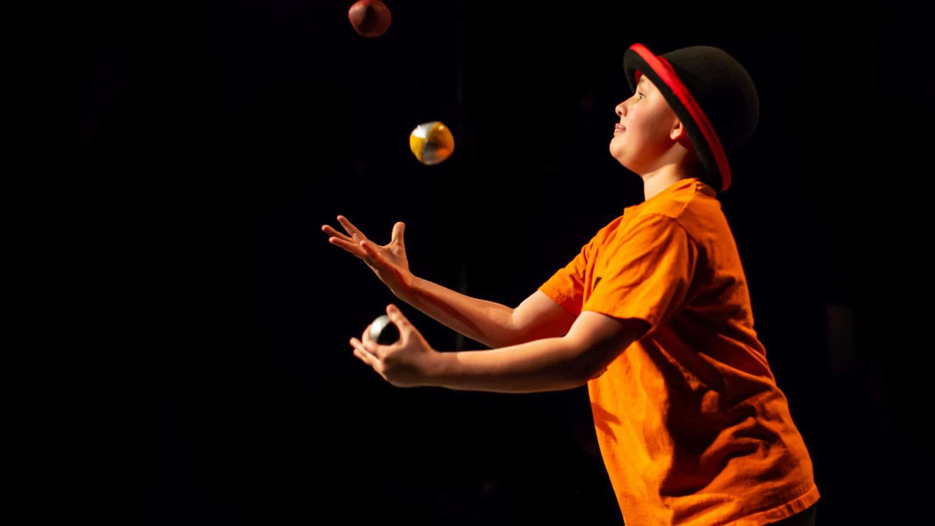 Young performer wearing a bowler hat, juggling