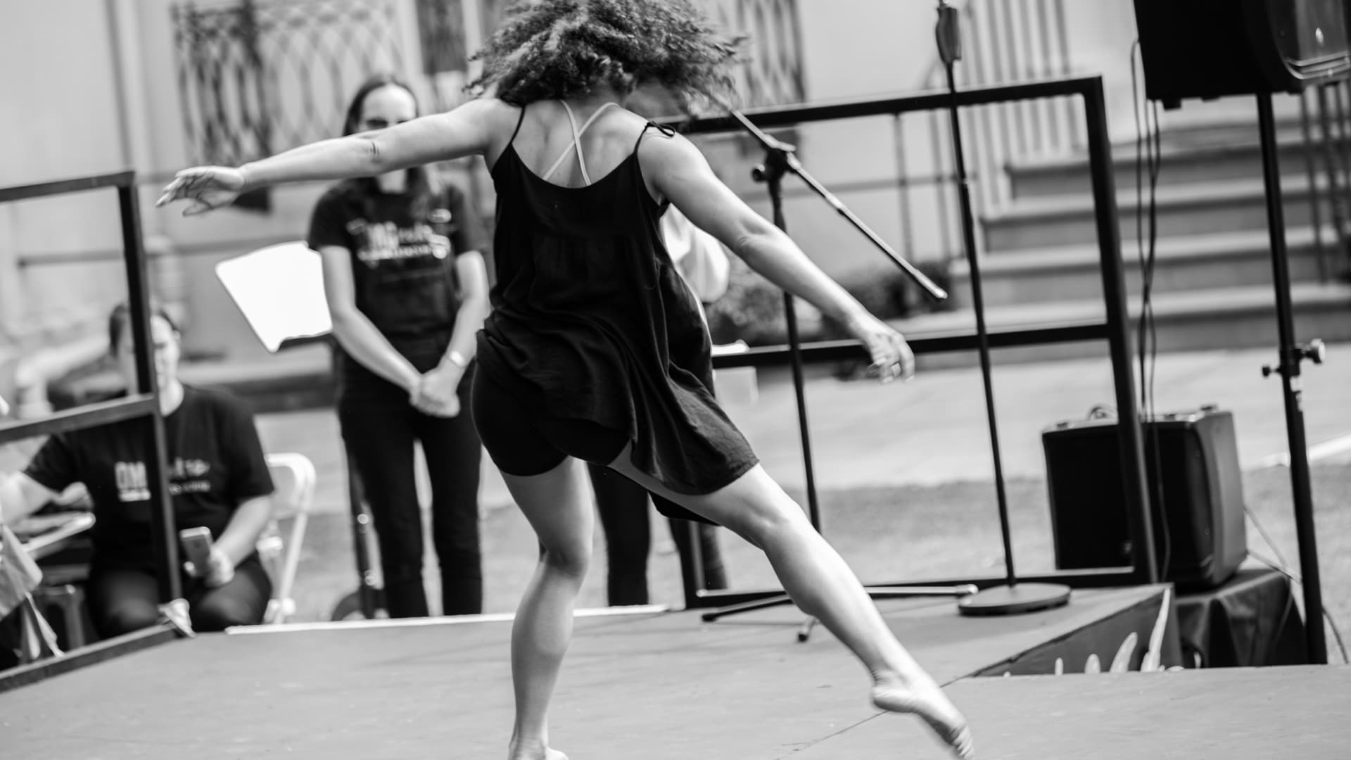 A dancer with long curly hair, wearing a long black sleeveless top and shorts