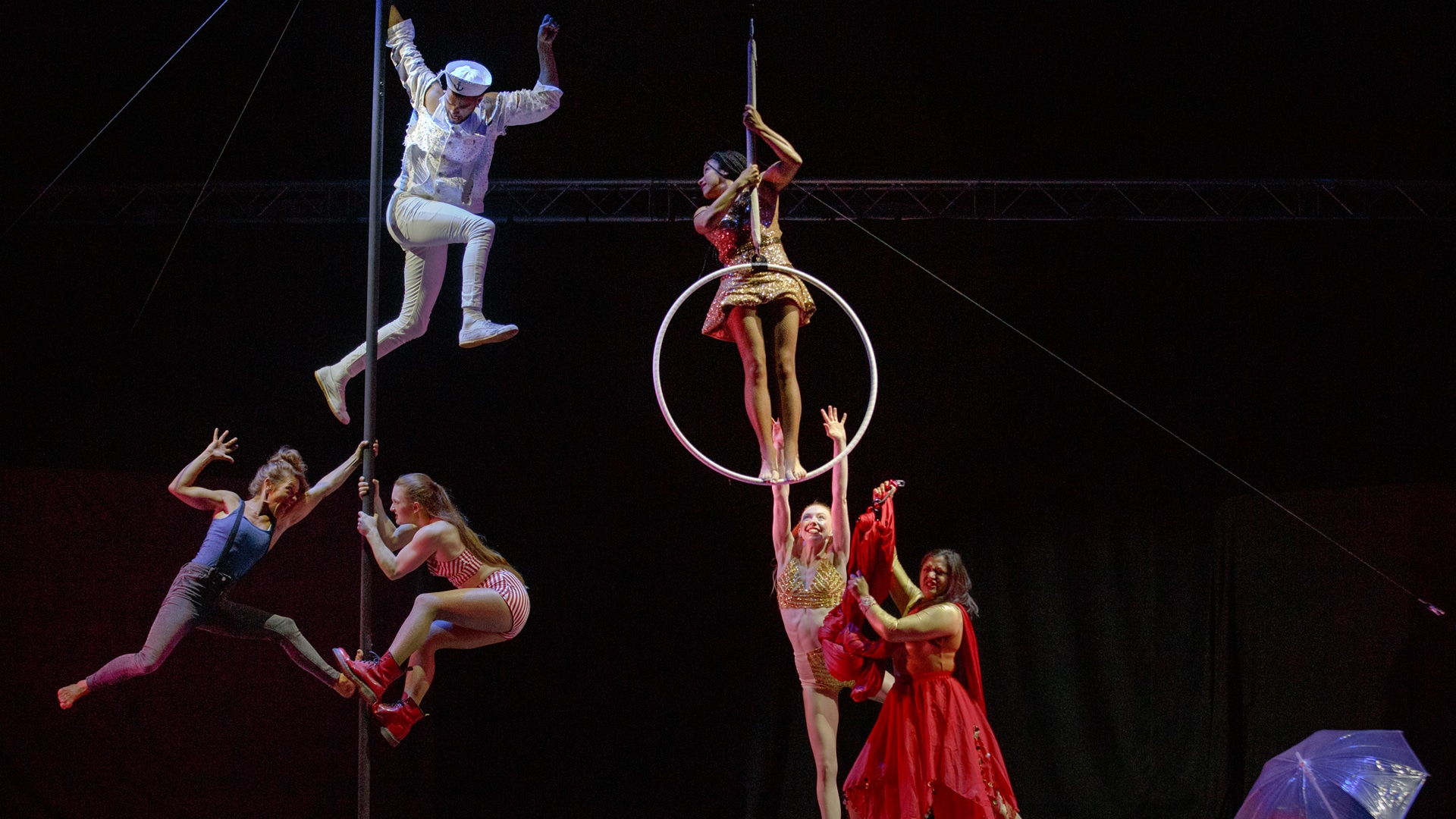 Aerial performers, three handing onto a pole, one stood in a hoop, two others reaching up to the hoop