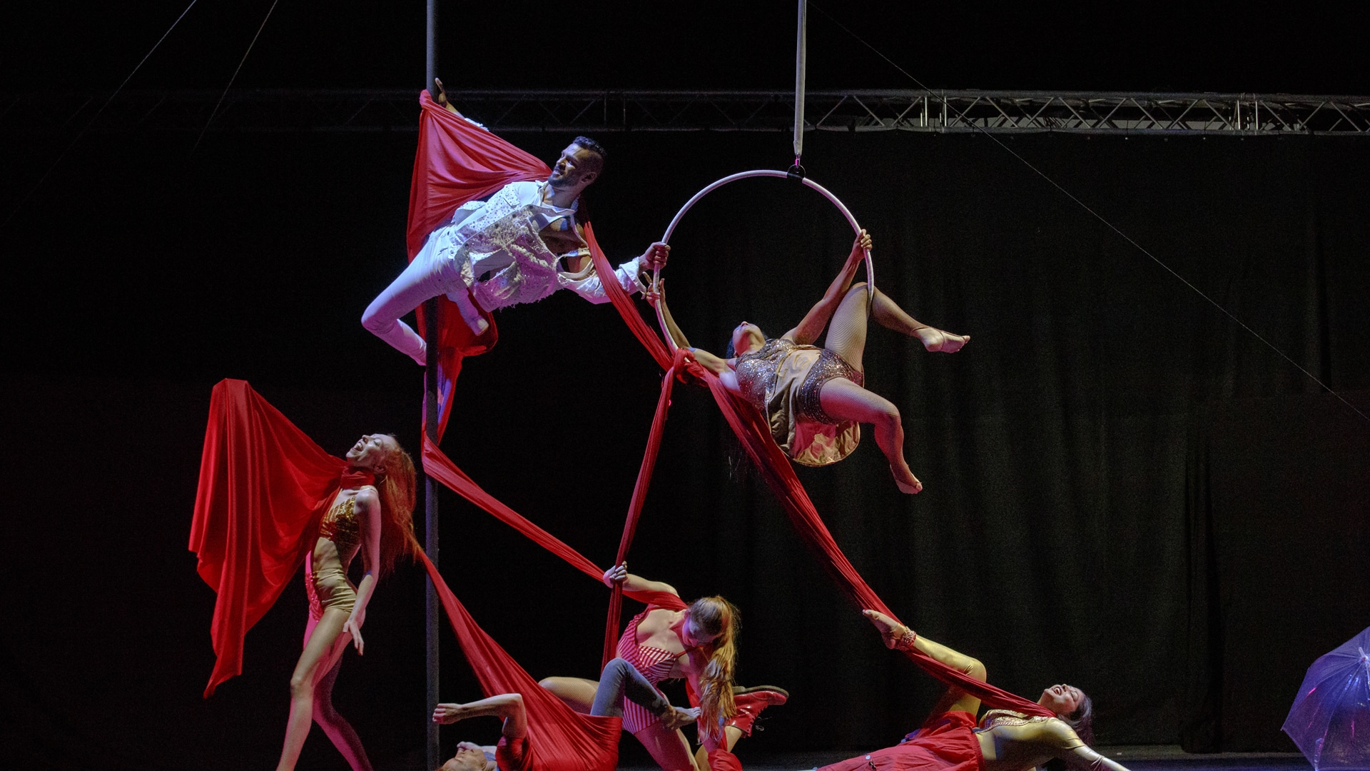 Aerial performers with a long red piece of material connecting them all