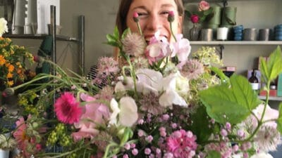 Nancy smiling holding a bouquet of flowers