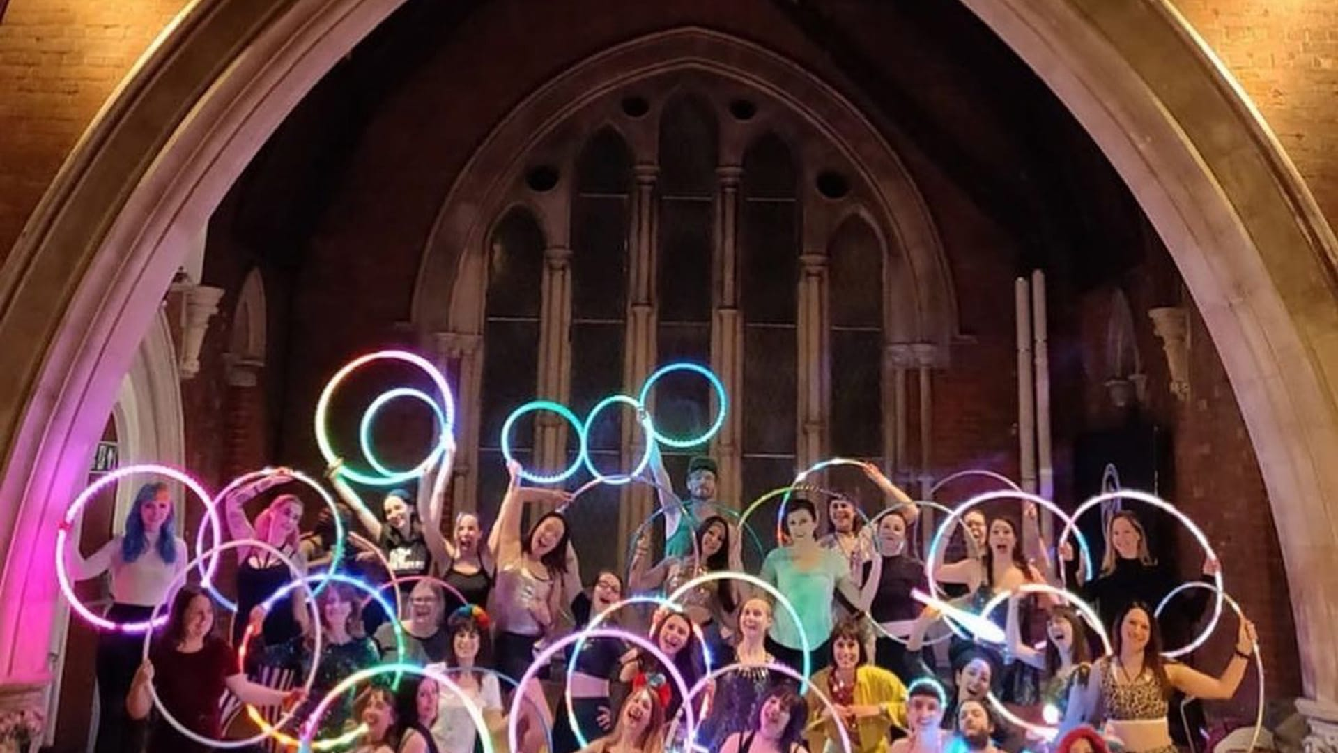 A large group of people holding light up hoops
