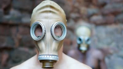two performers wearing gas masks - one standing in front of the other