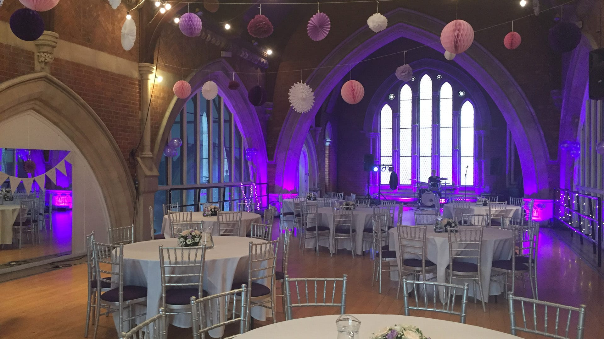 Studio 1 at Jacksons Lane prepared for a wedding - there's a stage for the band, bunting, and tables