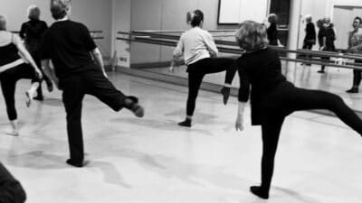 A class of dancers facing a dance studio wall mirror