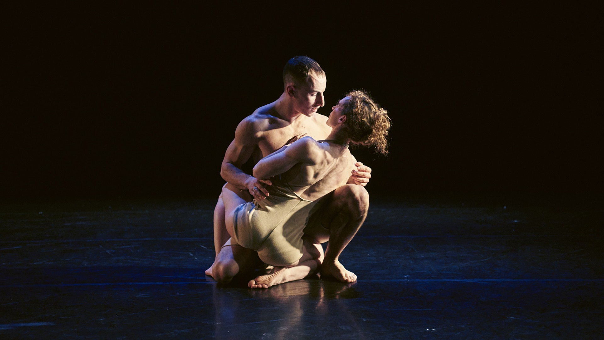 Nikki Rummer and JD Broussé gaze at each other, while crouching on the stage and holding one another