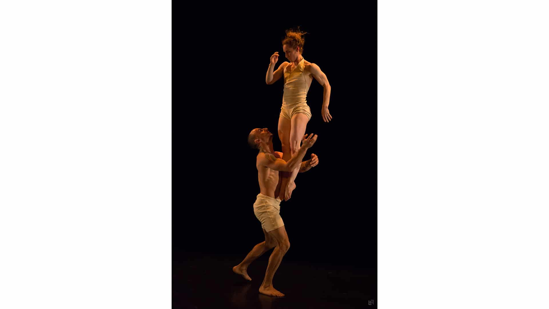 Nikki Rummer is in mid air, her legs pointed straight beneath her, while JD Broussé stands, his arms encircled around her legs, ready to catch her