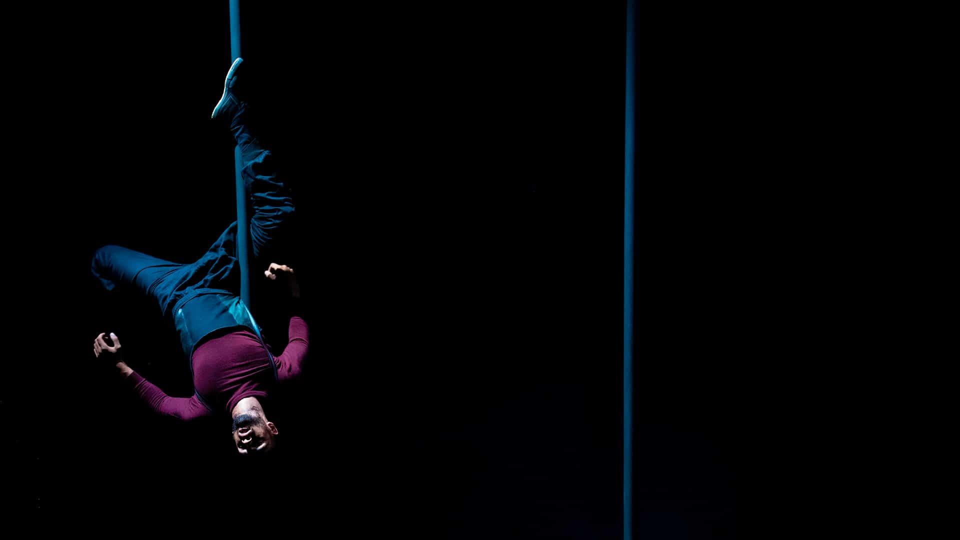 Sadiq Ali hangs upside down from a Chinese pole