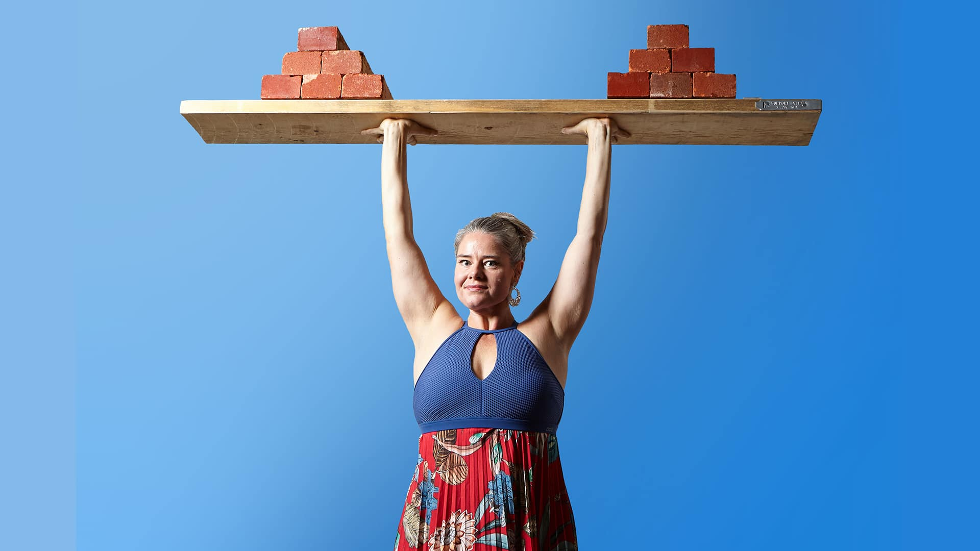 Charmaine Childs stands with her arms high above her head balancing a plank of wood on which a pile of bricks have been stacked on either end